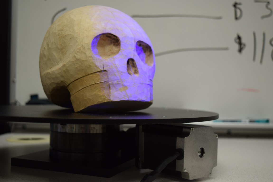 The skull model for the Trouvé pin, carved by Nicole Clouston, resting on the servo-driven turntable. The HDI 120 3D scanner uses structured-light, blue-LED technology to take high resolution images of the object as the turntable spins. Image care of the MLab