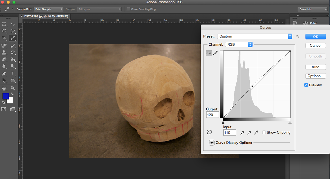 Image of a carved, wooden skull being edited using the curves tool in Photoshop